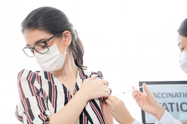 La donna indossa una maschera facciale contro il personale medico e infermieristico covid19 che usa la siringa per iniettare il vaccino