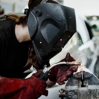Femmina che salda un pezzo di metallo in garage