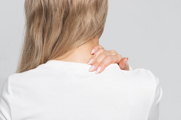 Donna in top bianco con dolore al collo e alla schiena.
