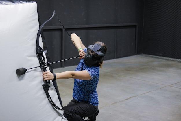 Femmina con arco di frecce di balestra. l'arciere prende la mira, tiratore scelto. club di balestra.