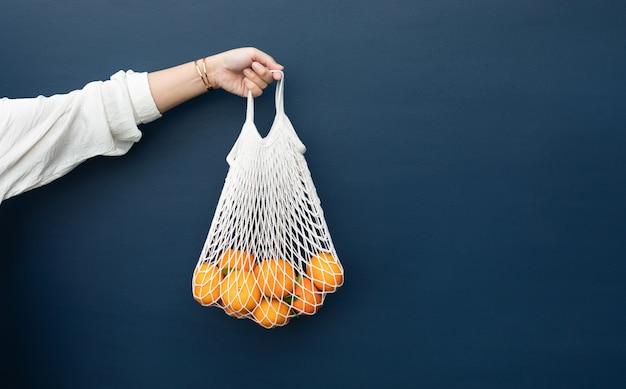 Femmina con arancia fresca dal giardino in borsa all'uncinetto