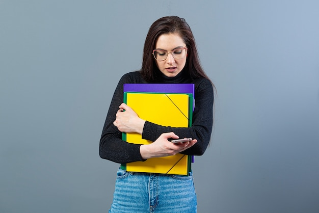 Femmina con lo smartphone che tiene un cartelle colorate con documenti, isolato sulla superficie scura