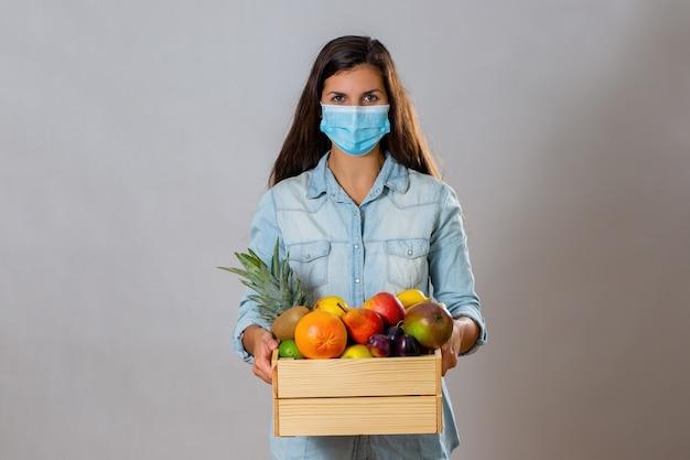 Femmina con mascherina chirurgica che tiene la scatola di legno piena di frutta fresca