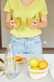 La mano della donna femminile tiene due bicchieri di limonata fresca di agrumi e rosmarino, bevanda estiva, acqua salutare disintossicante.