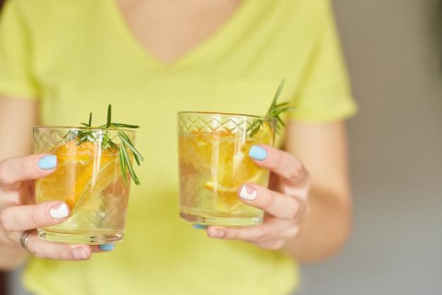 La mano della donna femminile tiene due bicchieri di limonata fresca di agrumi e rosmarino, bevanda estiva, acqua salutare
