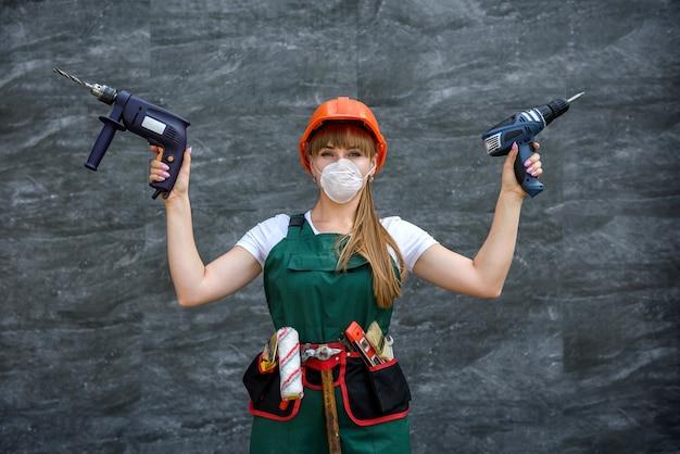 La lavoratrice tiene il trapano in mano su sfondo grigio. concetto di costruzione, riparazione, ristrutturazione.
