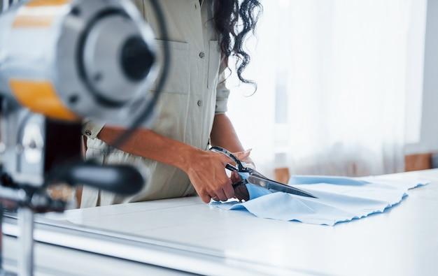 La lavoratrice è nella fabbrica di cucito durante il giorno per tagliare il panno con le forbici.