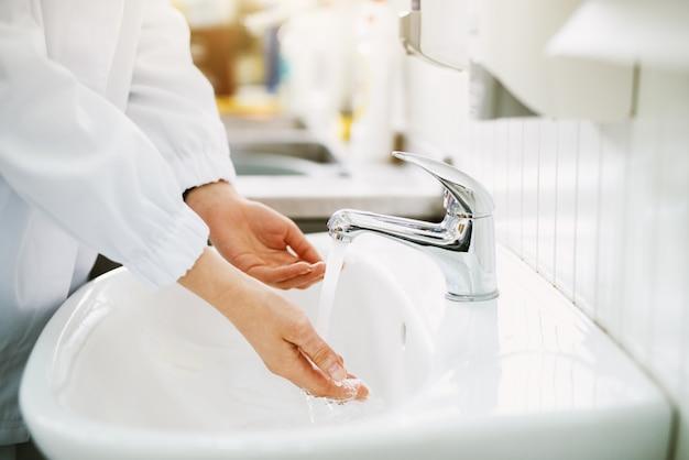La lavoratrice sta lavando le mani prima del lavoro in un lavandino del bagno.