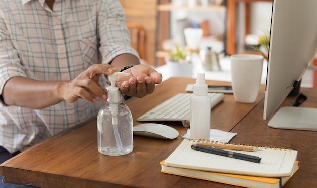 La lavoratrice seduta in ufficio a casa usa un disinfettante per le mani contro la pandemia di coronavirus