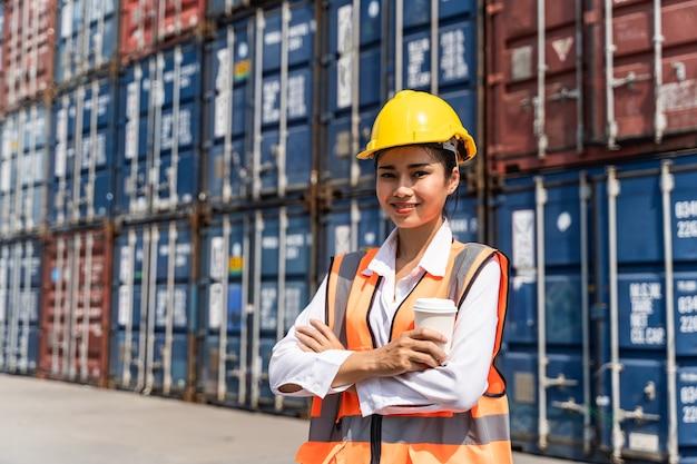 La lavoratrice in piedi e indossa un casco giallo controlla il carico e controlla la qualità dei container dalla nave da carico per la spedizione di importazione ed esportazione