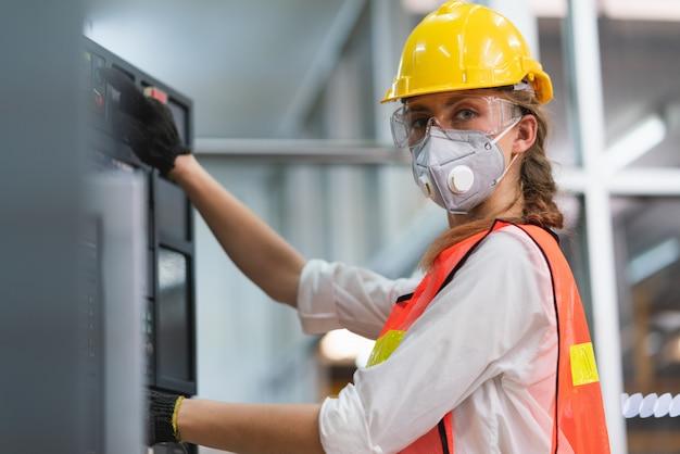 Lavoratrice con la maglia di sicurezza e casco giallo sul lavoro