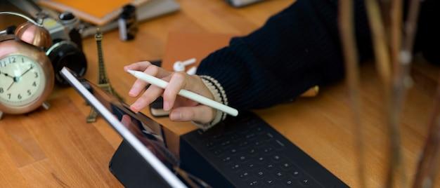 Lavoratrice che lavora con la compressa digitale sulla scrivania di legno con i rifornimenti e le decorazioni