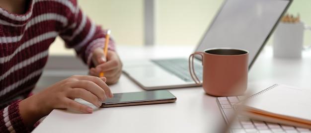 Donna che lavora con mock up laptop, smartphone, notebook e tazza di caffè sul tavolo bianco