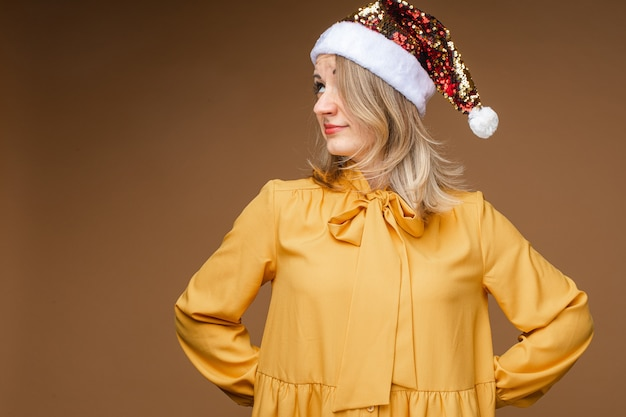 Donna in abiti gialli con capelli biondi che nasconde un oggetto dietro di sé e guarda di lato. anno nuovo concetto