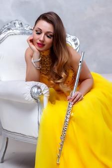 Donna in abito giallo con flauto su bianco