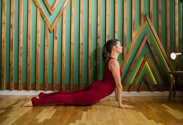Insegnante di yoga femminile in una tuta sportiva bordeaux esegue esercizi per una schiena sana in palestra