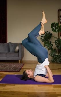 Yogi femminile in abiti sportivi esegue una posa invertita su una stuoia in una stanza
