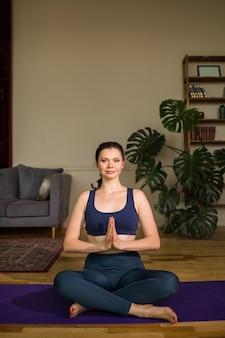 Yogi femminile in abiti sportivi si siede nella posizione del loto su un materassino yoga in una stanza