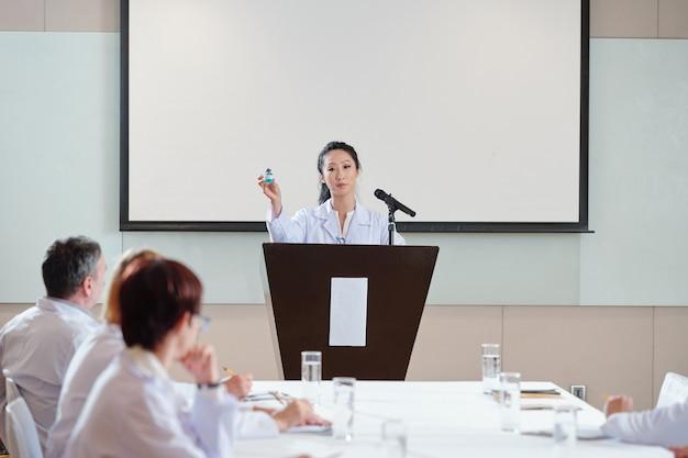 Giovane scienziata asiatica in piedi alla tribuna alla conferenza medica e parlando del nuovo vaccino covid-19