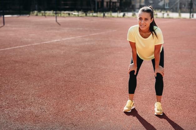 Giovane atleta femminile con capelli scuri che riposa con le mani sulle ginocchia dopo la corsa mattutina sulla corte rossa.