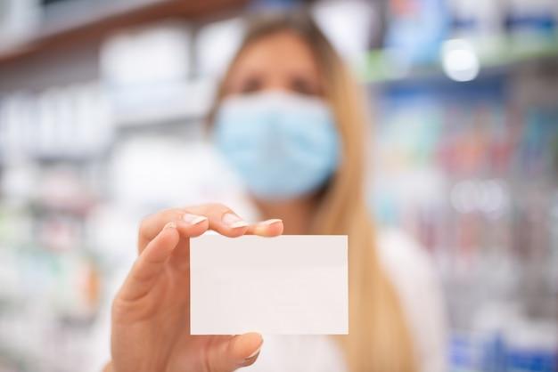 Giovane femmina mascherata per farmacista covid o coronavirus che mostra un biglietto da visita vuoto