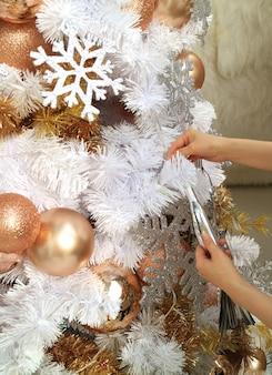 Mani femminili che tengono un ornamento per decorare lo splendido albero di natale bianco e oro