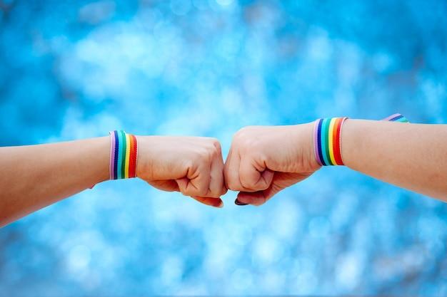 Una femmina che fa il segno della mano con il braccialetto di colori dell'arcobaleno su fondo vago