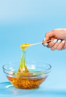 Mani femminili estraggono la pasta di zucchero per zuccherare con una spatola di legno sul blu