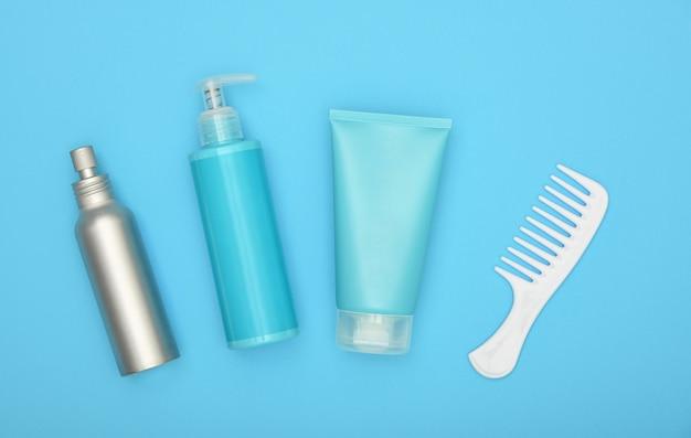 Cura di bellezza femminile la disposizione piatta del trattamento dei capelli impostato su sfondo blu, vista dall'alto in elevazione, direttamente sopra