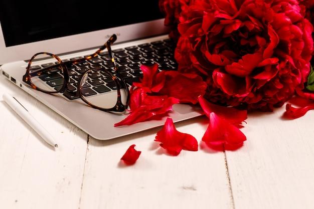 Modello di business femminile con laptop rosa, bouquet di peonie