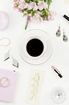 Piano femminile disteso con accessori moda e fiori sul piano del tavolo bianco