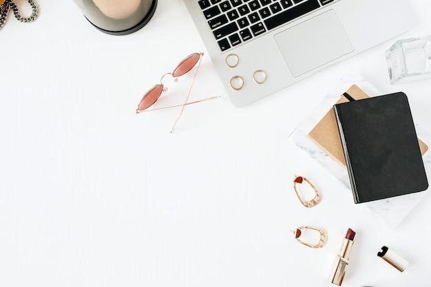 Area di lavoro femminile moderna home office scrivania con laptop, rossetto, occhiali da sole e accessori su superficie bianca