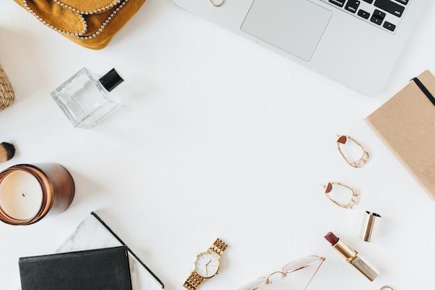 Area di lavoro femminile moderna home office scrivania con laptop, profumo, orologio, rossetto, pennello e accessori su superficie bianca