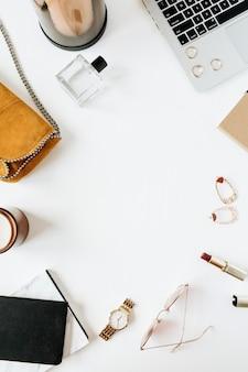 Area di lavoro di scrivania in stile moderno femminile con laptop e accessori su superficie bianca
