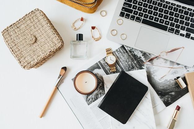 Area di lavoro di scrivania in stile moderno femminile con laptop, accessori su bianco
