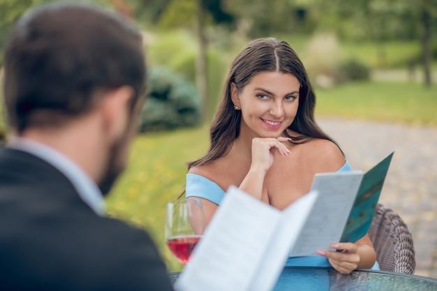 Donna piuttosto sorridente femminile con menu guardando con interesse l'uomo in costume seduto di fronte