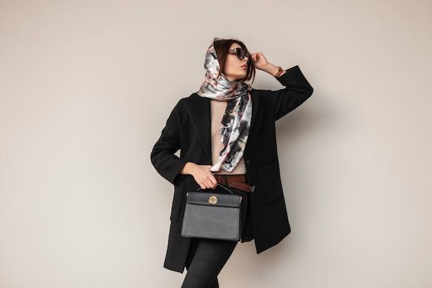 Giovane donna modello elegante femminile in occhiali da sole alla moda in lussuosi vestiti neri alla moda con borsa in pelle con elegante sciarpa sulla testa vicino al muro sulla strada. bella ragazza. signora d'affari