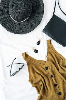 Composizione di moda estiva femminile con cappello, camicetta, orecchini, borsa e occhiali da sole su superficie bianca