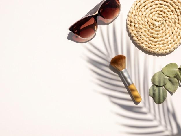La scrivania bianca estiva femminile distesa piatta con copia spazio, cosmetici e occhiali da sole