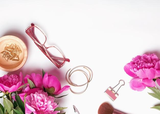 Concetto di lavoro femminile con peonie rosa, articoli di cancelleria e bicchieri