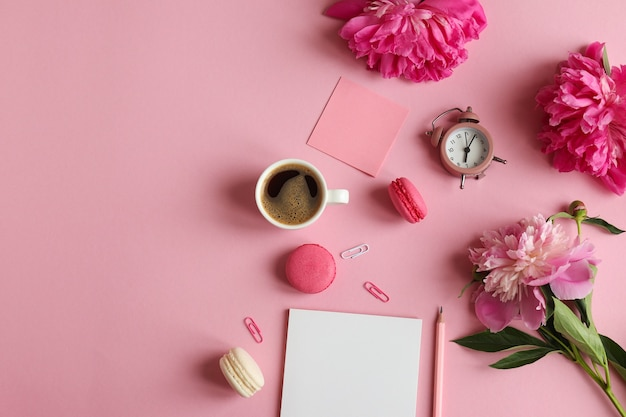 Posto di lavoro femminile con blocco note matita sveglia fiori di peonia foglietti adesivi caffè macarons