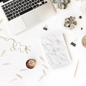 Area di lavoro femminile con laptop, diario in marmo, penna dorata su sfondo bianco.