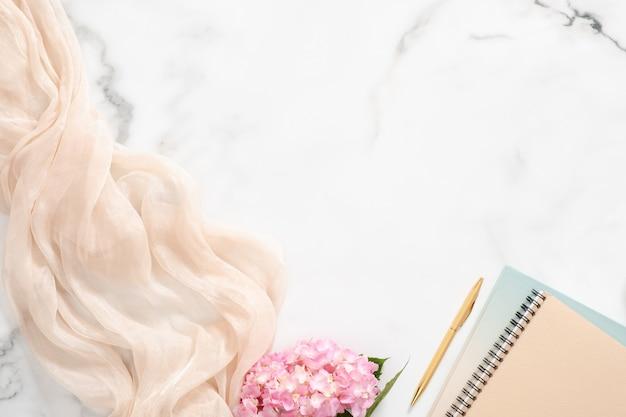 Area di lavoro femminile con fiori di ortensia rosa, coperta pastello, blocco note di carta e accessori su fondo di marmo