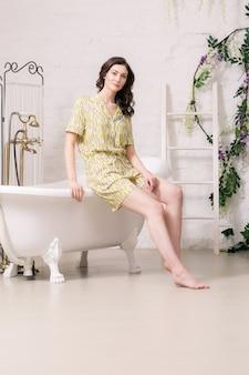 Giovane ragazza bruna femminile che si siede sul bordo della vasca da bagno nel bagno alla moda bianco.
