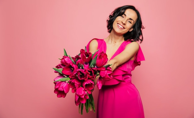 Femminilità. foto ravvicinata di una ragazza in un abito fucsia, che tiene un mazzo di tulipani rosa tra le mani tese, guardando con gioia nella fotocamera.