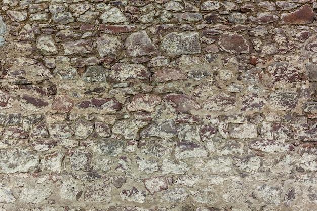 Recinzioni e muri delle case sono nei villaggi e nelle città della georgia fatti di diversi tipi di pietra, sfondo di pietra naturale, struttura di pietra.