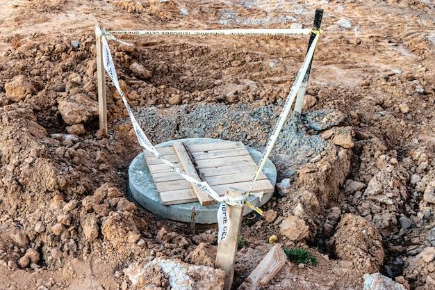 Recinzione del portello della fogna installato. area di riparazione del marciapiede recintato. sicurezza.