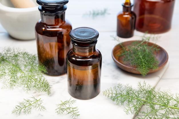 Olio essenziale di finocchio su bottiglie di ambra. olio alle erbe per la cura della pelle, aromaterapia e medicina naturale