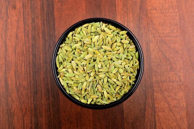 Semi di finocchio nella ciotola su fondo di legno, seme secco.