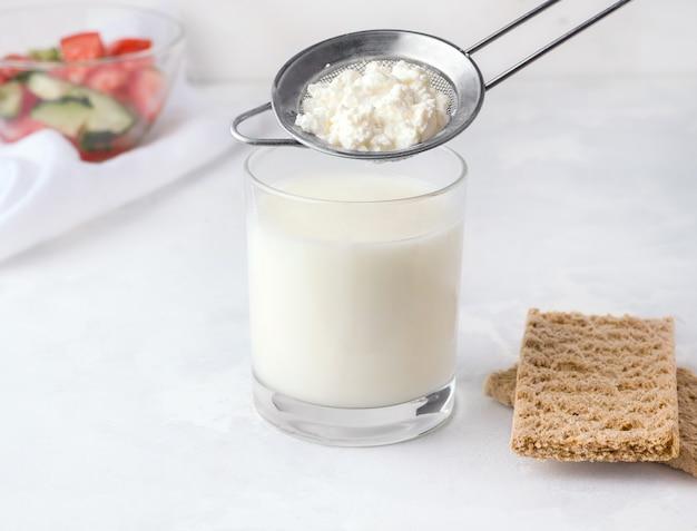 Bevanda fermentata kefir in un bicchiere con granuli di batteri